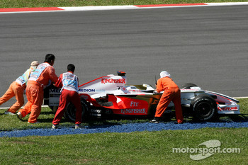 Marshalls push away the car of Adrian Sutil, Force India F1 Team after he stopped on track