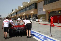 McLaren Mercedes, MP4-23 is pushed down the pitlane past Scuderia Ferrari