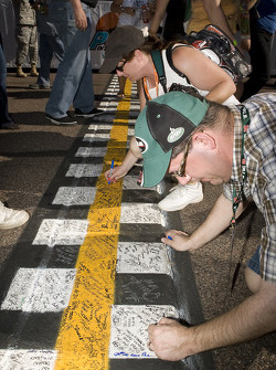 Fans sign the start/finish line before the race