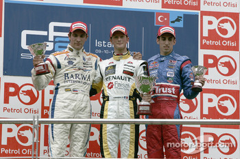 Romain Grosjean celebrates on the podium with Vitaly Petrov and Sebastien Buemi
