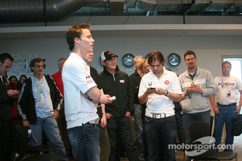 Alex Lloyd, Scott Dixon and Dan Wheldon play video games during the rain delay