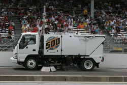 A sweeper cleans up the oil dry on the track
