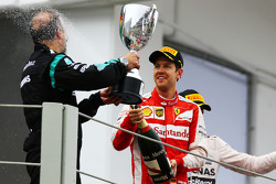 Sebastian Vettel, Ferrari celebrates his third position with Jimmy Waddell, Mercedes AMG F1 Composite Inspector on the podium