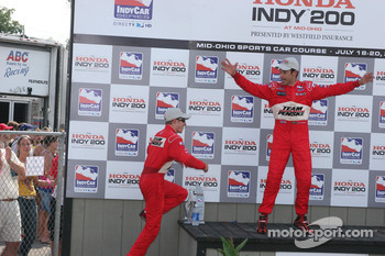 Podium: Helio Castroneves clowns around as race winner Ryan Briscoe climbs onto the podium