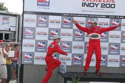 Podium: Helio Castroneves clowns around as race winner Ryan Briscoe climbs onto the podium