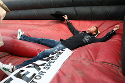 Scott Speed takes a flop on the inflatable safety mat after his maiden ride on a mechanical bull in the Fort Worth Stockyards