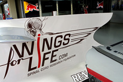 An Red Bull Racing RB4 engine cover in front of the Red Bull Racing gargae