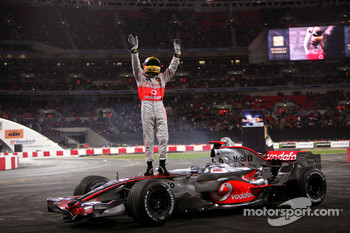 Lewis Hamilton stands on top of his McLaren Mercedes F1 car as he waves to the crowd