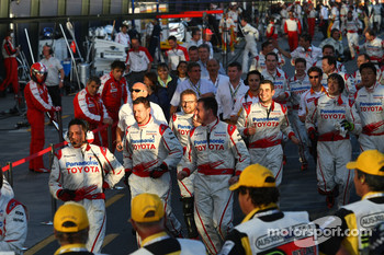 The Toyota team run for the podium