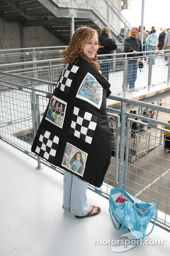 A fan warms up with a blanket decorated with images of Danica Patrick