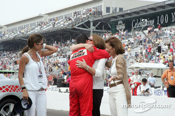 Race winner Helio Castroneves gets a hug from friends and family