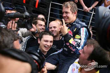 Race winner Sebastian Vettel celebrates with Red Bull Racing team members