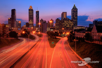 The Atlanta skyline at dusk with traffic streaming through the city