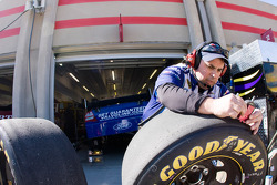 A crew member works on tires during practice