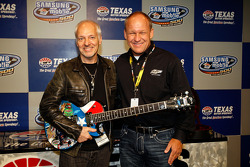Musician Peter Frampton poses withe artist Sam Bass after Frampton was presented with a quitar designed by Bassduring a press conference