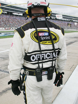 NASCAR Official has two radios, tire gage and notebook ready for action