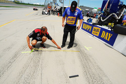 Crew members from Dreyer and Reinbold Racing make a measurement