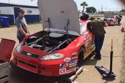 Crew Chief RJ Godett supervises Cameron Millard's car while Michael Millard confers with his son.