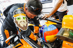An engineer helps Fernando Alonso, McLaren MCL33, strap in to his car