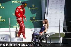 Third place Kimi Raikkonen, Ferrari, receives his trophy from Nathalie McGoin on the podium