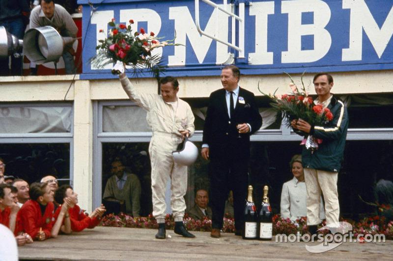 De gauche à droite : Bruce McLaren, Henry Ford II et Chris Amon sur le podium après la victoire de Ford aux 24 Heures du Mans 1966
