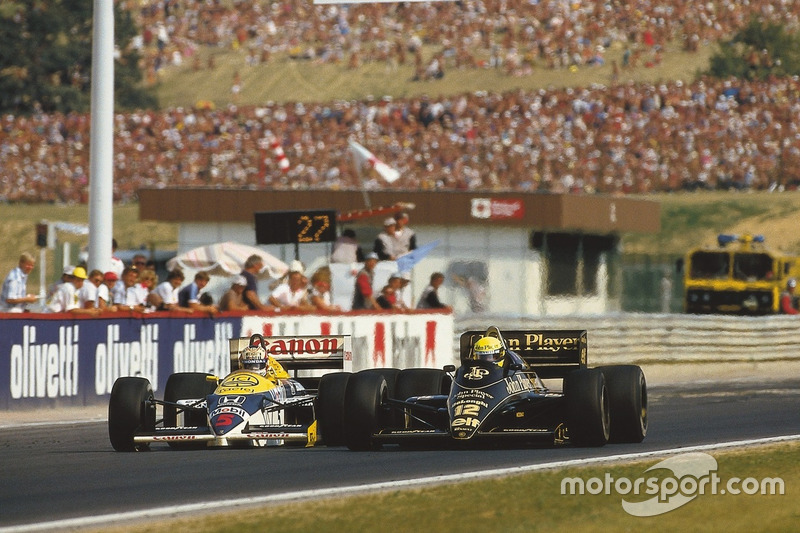 Ayrton Senna (Lotus 98T Renault) overtakes Nigel Mansell (Williams FW11 Honda). They finished in 2nd and 3rd positions respectively
