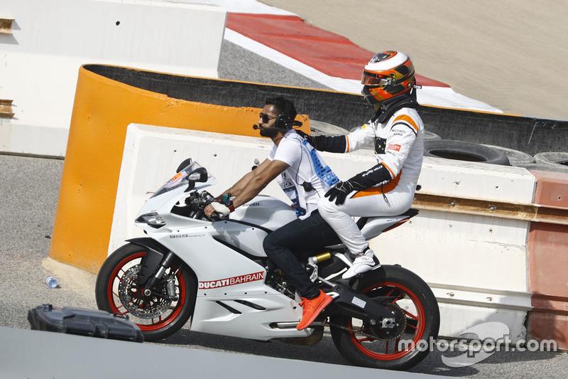 Stoffel Vandoorne, McLaren, gets a lift back on a motorbike
