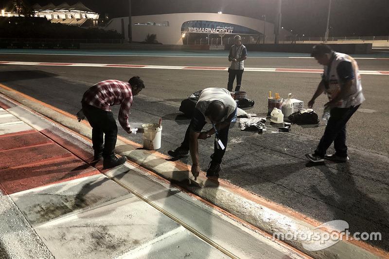 Pekerja memperbaiki kerb trek Yas Marina, Abu Dhabi
