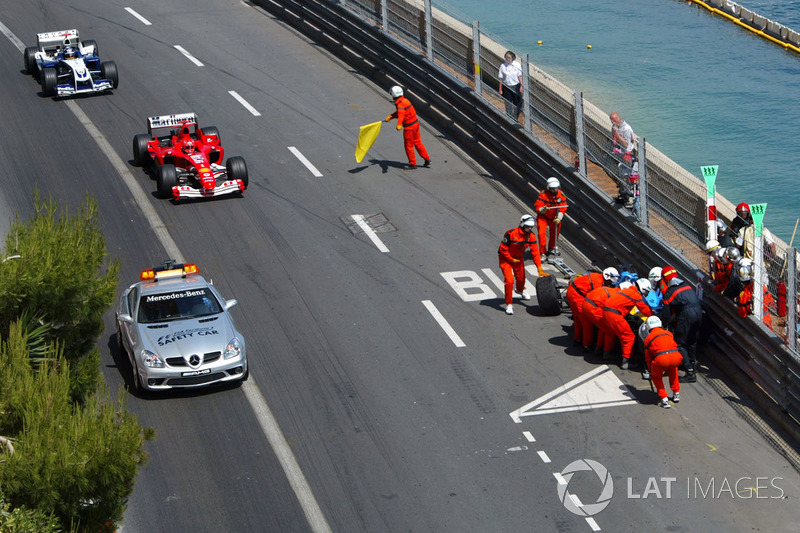El Renault R24 de Fernando Alonso es atendido por los comisarios tras su accidente a la salida del tunel, y Michael Schumacher, con el Ferrari F2004, sigue al Safety Car delante de Juan Pablo Montoya, Williams BMW FW26
