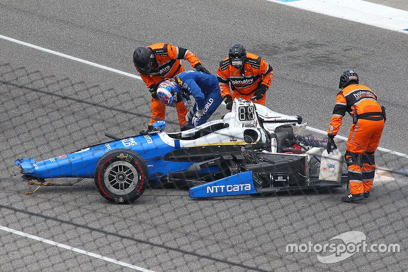 Гонщик Chip Ganassi Racing Honda Скотт Диксон выбирается из автомобиля после аварии