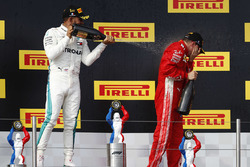 Lewis Hamilton, Mercedes AMG F1, 1st position, sprays Kimi Raikkonen, Ferrari, 3rd position, with Champagne on the podium