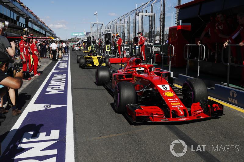 Sebastian Vettel, Ferrari SF71H, leads Carlos Sainz Jr., Renault Sport F1 Team R.S. 18. down the pit lane