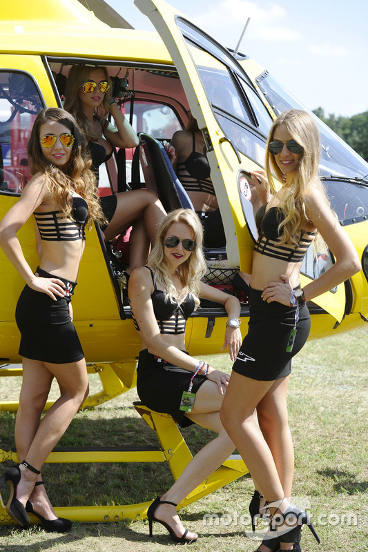 Lovely grid girls pose with an helicopter