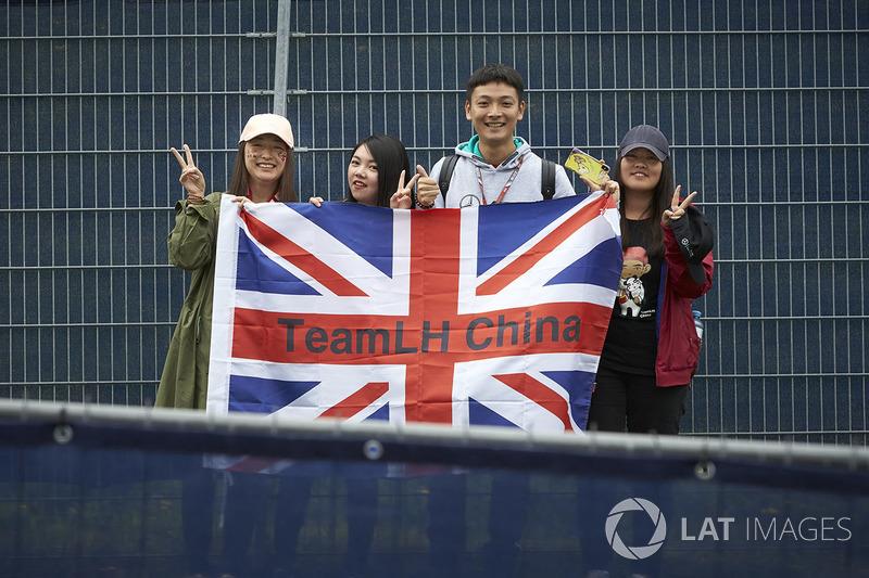 Los fanáticos de Lewis Hamilton, Mercedes AMG F1 W09, posan con una bandera