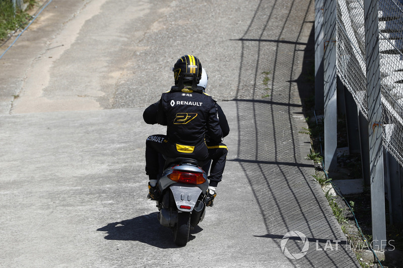 Nico Hulkenberg, Renault Sport F1 Team R.S. 18. receives a lift back to the pits on a moped