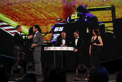 Enaam Ahmed collects an Award from David Coulthard