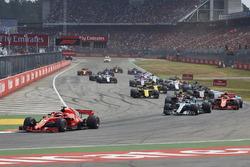 Sebastian Vettel, Ferrari SF71H, voor Valtteri Bottas, Mercedes AMG F1 W09, Kimi Raikkonen, Ferrari SF71H, Max Verstappen, Red Bull Racing RB14, Kevin Magnussen, Haas F1 Team VF-18, Nico Hulkenberg, Renault Sport F1 Team R.S. 18, en de rest van het veld na de start