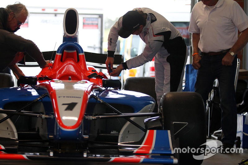 The retro feel goes as far as the driver working on the car