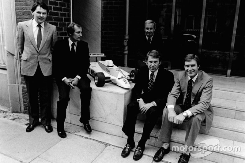 L to R: McLaren International John Barnard, Ron Dennis Teddy Mayer behind Tyler Alexander and Creighton Brown pose with a model of the McLaren MP4-1