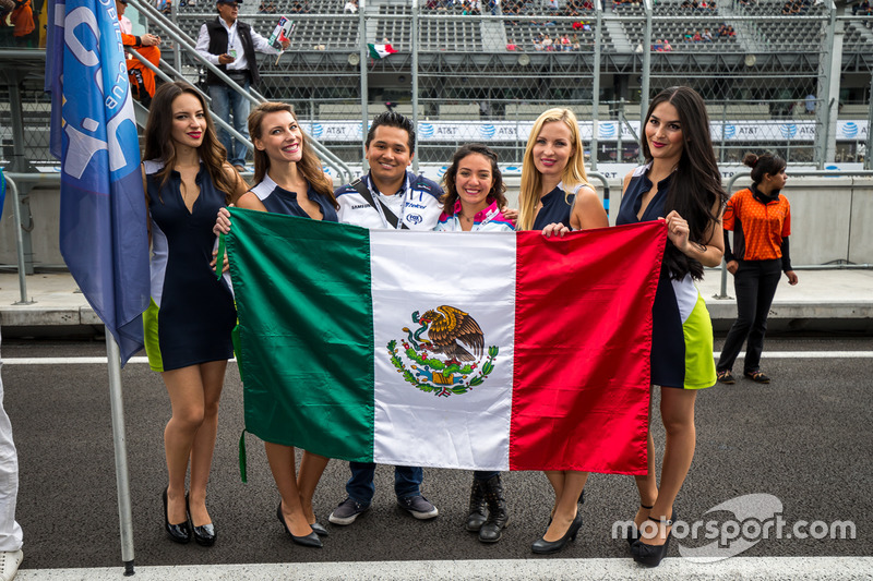 Fans taking their picture with the grid girls and a Mexican flag