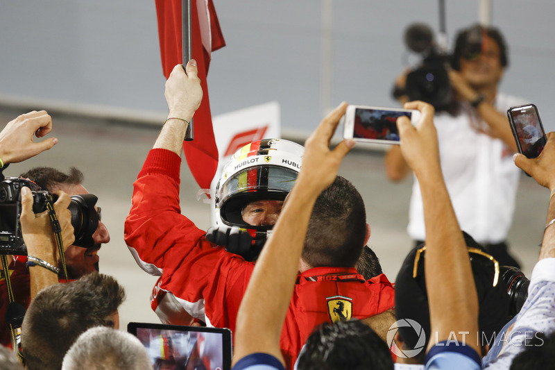 Team members capture the arrival of Sebastian Vettel, Ferrari, 1st position, in Parc Ferme
