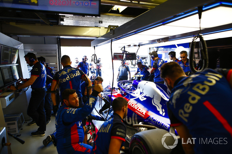 Mechanics work on the Brendon Hartley Toro Rosso in the team's garage