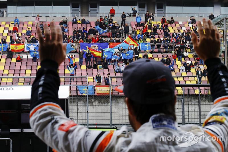 Fernando Alonso, McLaren, waves to fans in a grandstand