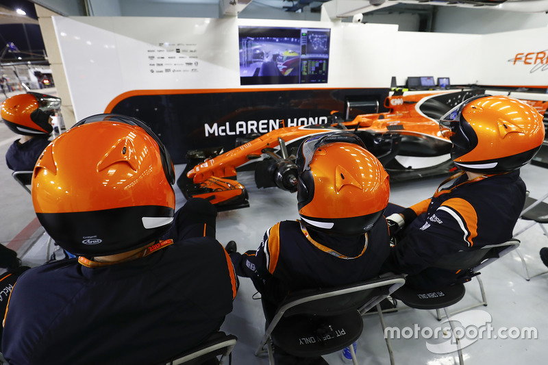 Los mecánicos de McLaren ven la carrera en el garaje con el auto de Stoffel Vandoorne, McLaren MCL32