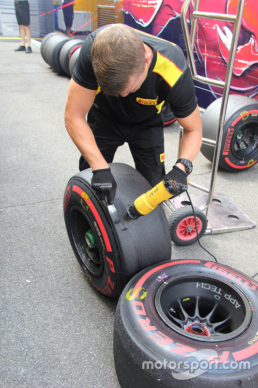 Pirelli technitian scraping the tyres used in the practice session