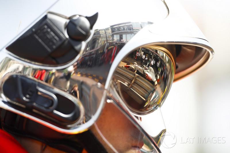 Romain Grosjean, Haas F1 Team VF-18, as seen in the reflection of a marshals helmet