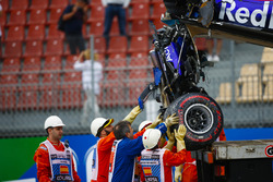 Marshals remove the damaged car of Brendon Hartley, Toro Rosso STR13, from the circuit as the gearbox hangs off the back