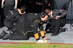 McLaren mechanics clean aero paint from the garage floor