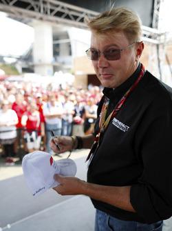 Mika Hakkinen signs a cap for fans