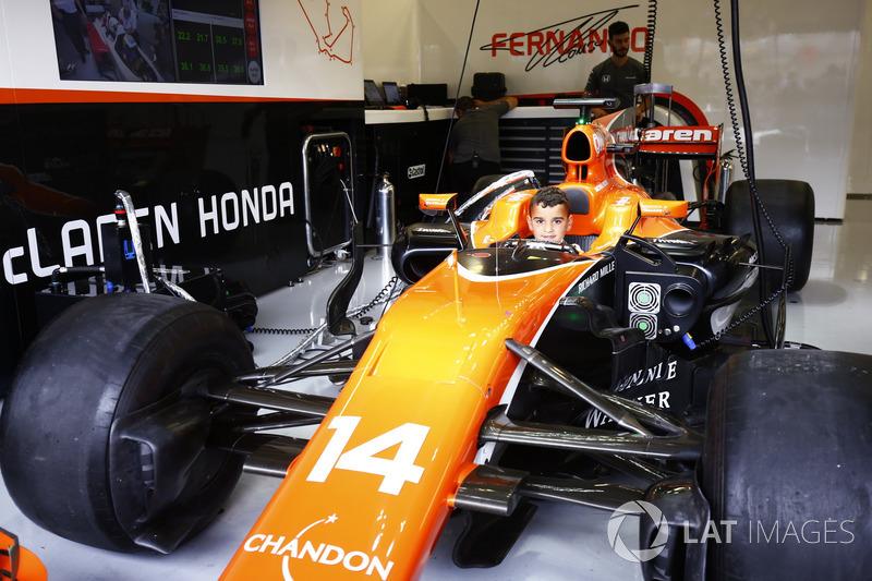 Un joven fan se sienta en la cabina de Fernando Alonso McLaren MCL32